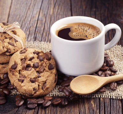 Nutella chocolate chip cookies sitting next to a cup of coffee with a wooden spoon laying beside it.