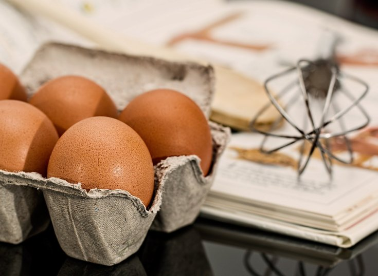 Carton of brown eggs sitting on the counter with a wooden spoon, tea towel, and whisk.